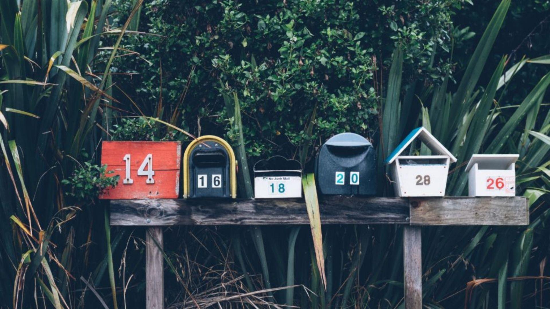 Verschiedene Briefkästen auf einem Holzbalken